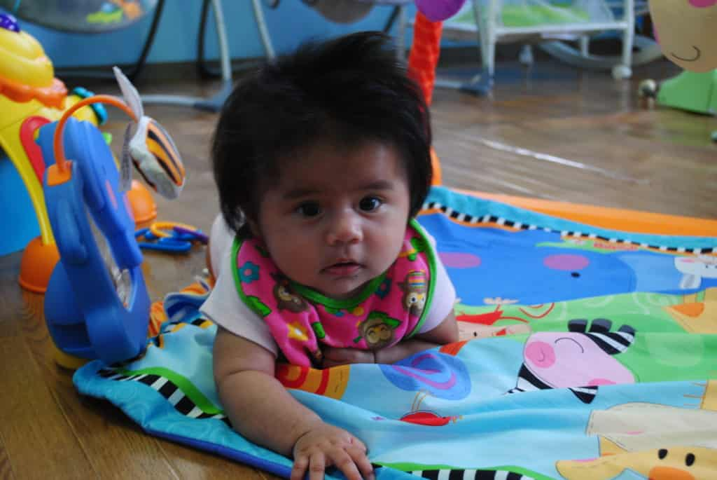 Baby crawling on mat at Sunshine Montessori School