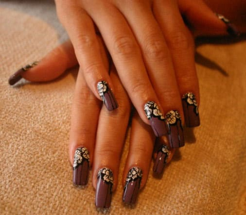 Woman's hands with purple and flower design nails