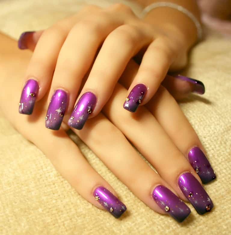 Woman's hands with metallic purple nails