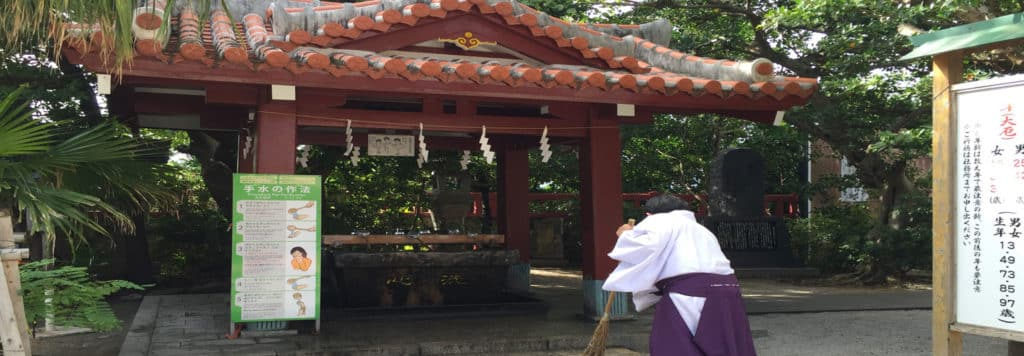 Lady sweeping ground at Naminoue Shrine