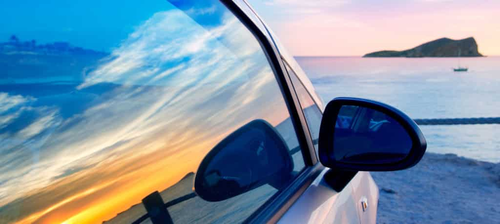 Car Parked on beach with sunset reflection in window