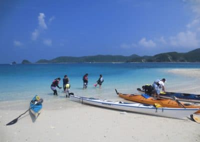 Canoes on Zamami beach with people in water